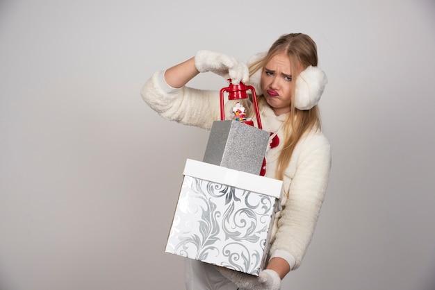 Blonde en pull blanc prenant un cadeau dans une boîte blanche.
