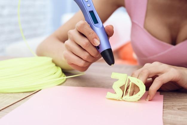 Blonde en robe rose dessine un stylo 3d.