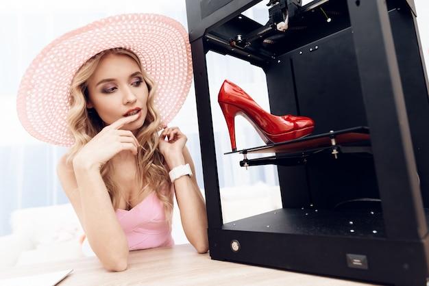 Blonde en robe rose regarde une chaussure rouge dans une imprimante 3d.