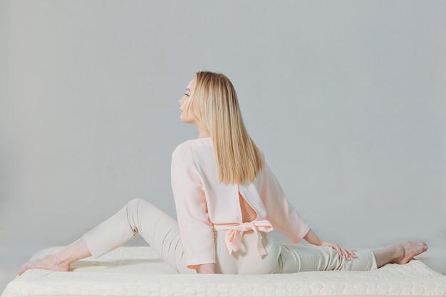 La blonde en rose est allongée sur le sol.