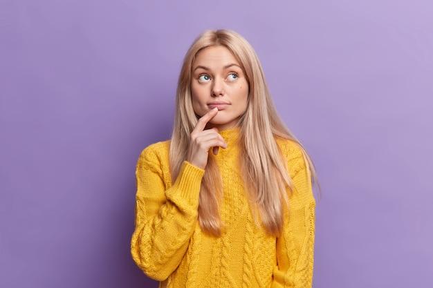 Blonde séduisante jeune femme européenne garde le doigt sur les lèvres regarde avec une expression pensive ci-dessus prend une décision importante construit des plans à l'esprit porte un pull jaune