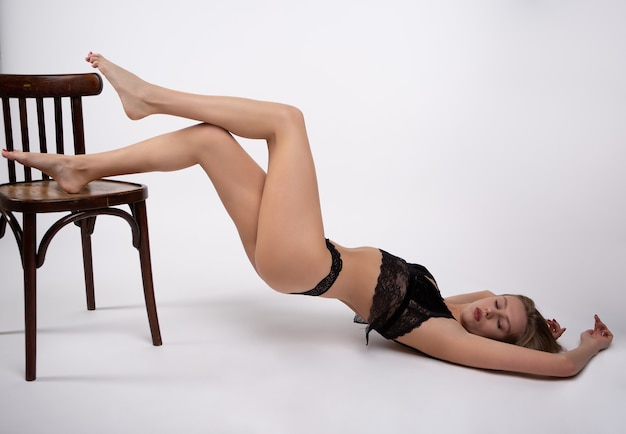 Blonde sensuelle en sous-vêtements sexy se trouve avec ses jambes pliées sur une chaise