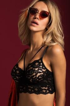 Blonde sexy à lunettes et sous-vêtements noirs sur un mur rouge