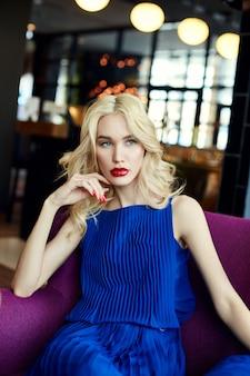 Blonde sexy en robe bleue assise au restaurant