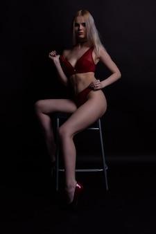 Blonde sexy en sous-vêtements en dentelle rouge est assise sur une chaise