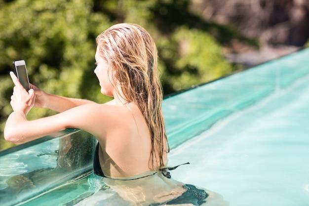 Blonde souriante à l'aide de smartphone dans la piscine par une journée ensoleillée