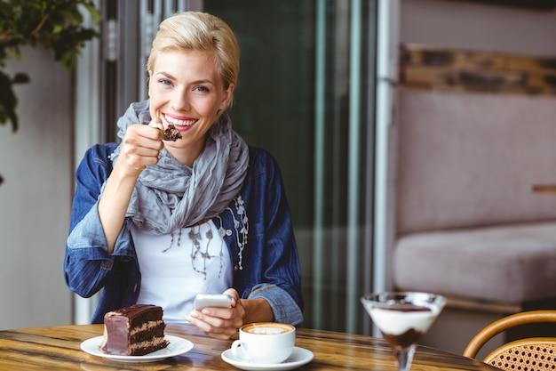 Blonde souriante appréciant un morceau de gâteau au chocolat