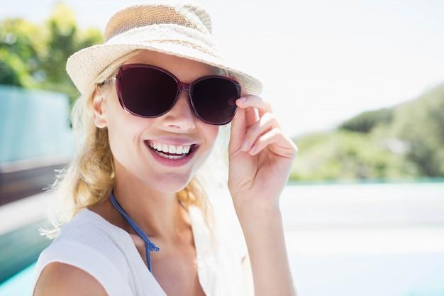 Blonde souriante avec chapeau et lunettes de soleil en regardant la caméra