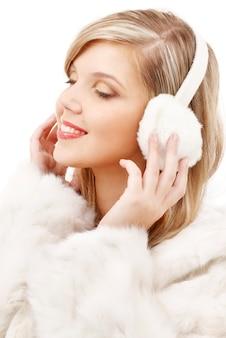 Blonde souriante dans des écouteurs à fourrure