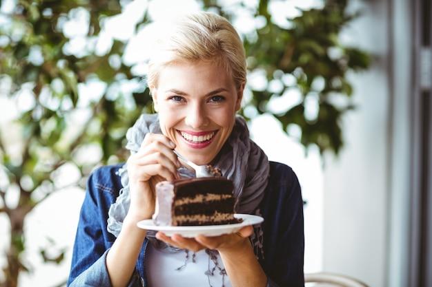 Blonde souriante prenant un morceau de gâteau au chocolat