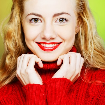 Blonde souriante en pull rouge