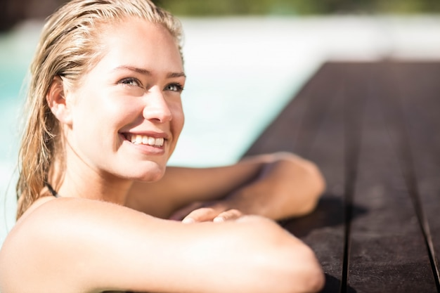 Blonde souriante se penchant sur le bord des piscines et levant