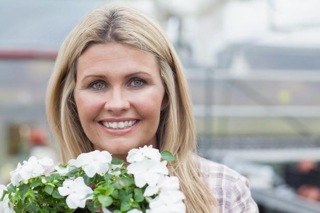 Blonde souriante tenant des fleurs blanches