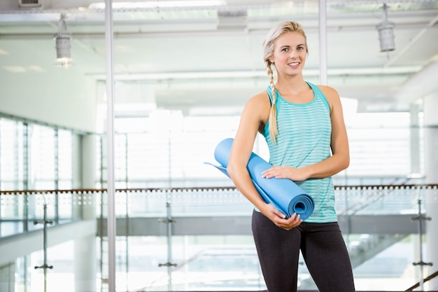 Blonde souriante tenant un tapis de yoga au centre de loisirs