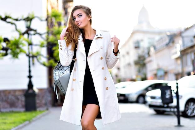Blonde superbe femme marchant seule au centre-ville, portant un manteau et une robe élégants décontractés, faisant du shopping seul, mode de style de rue.