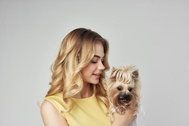 Blonde vêtue d'une robe jaune s'amuse avec un petit chien à la mode vue recadrée