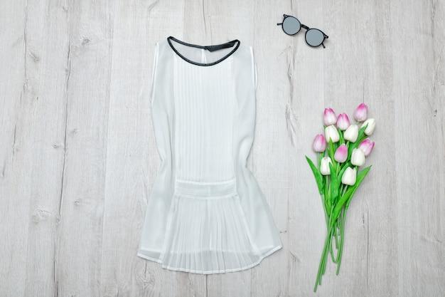 Blouse blanche, lunettes et un bouquet de tulipes. .