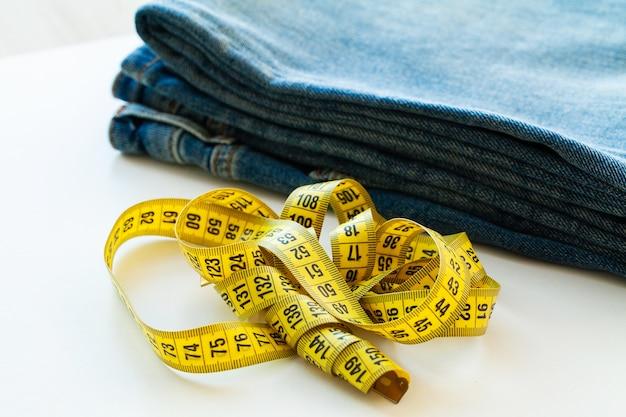 Blue jeans et ruban à mesurer sur blanc