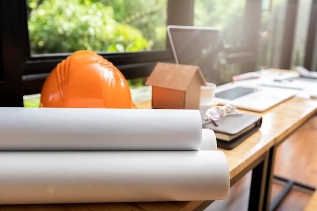 Blueprint avec casque et architectes maison modèle sur le bureau.