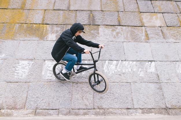 Bmx freestyle. un homme monte un mur sur un vélo bmch. astuces sur le mur