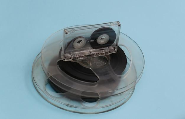 Bobine de bande magnétique audio et cassette audio sur pastel bleu.