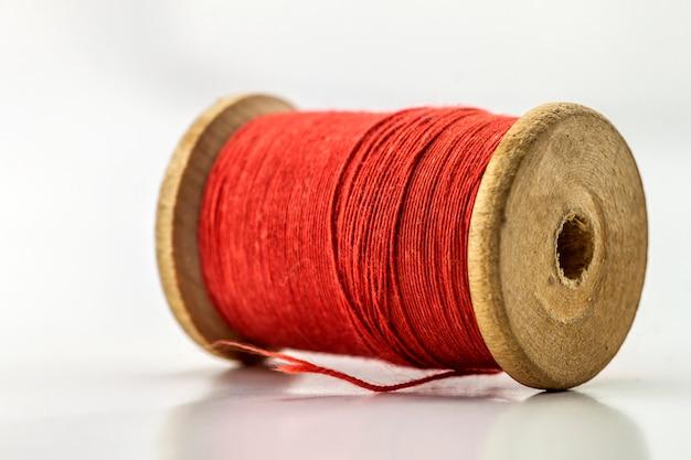 Bobine ou bobine de fil à coudre rouge isolé sur blanc. faible profondeur de champ. gros plan macro.