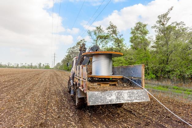 Bobine avec câble haute tension monté sur camion à roues. installation de câble sur supports haute tension