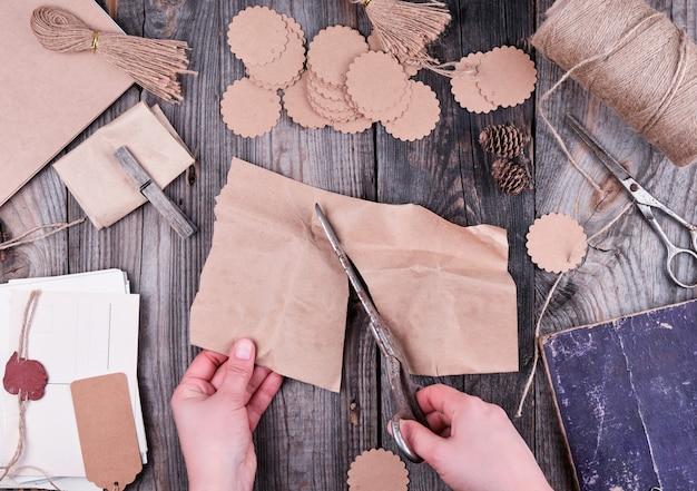 Bobine de corde marron, étiquettes en papier et vieux ciseaux sur bois gris