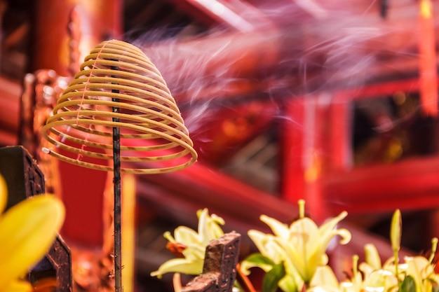 Bobine d'encens brûlant avec de la fumée blanche dans le fond du temple bouddhiste
