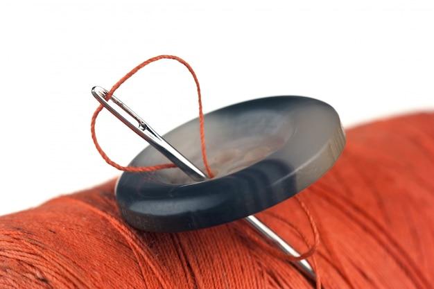 Bobine de fil et boutons isolé sur une surface blanche