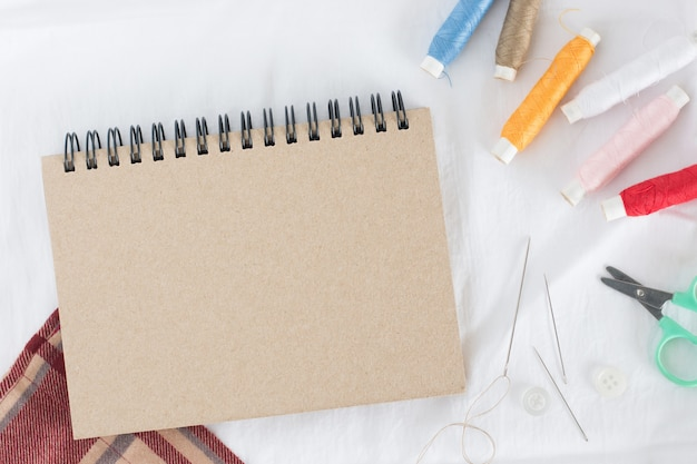 Bobine de fil de nombreuses couleurs avec aiguille, petits ciseaux et cahier marron sur tissu blanc
