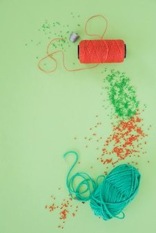 Dé; bobine de fil; perles rouges et vertes et laine sur fond vert