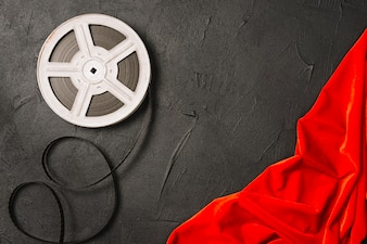 Bobine de film près de tissu rouge