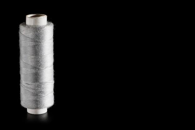 Bobine de fils de soie à coudre gris isolé sur fond noir, gros plan, copyspace