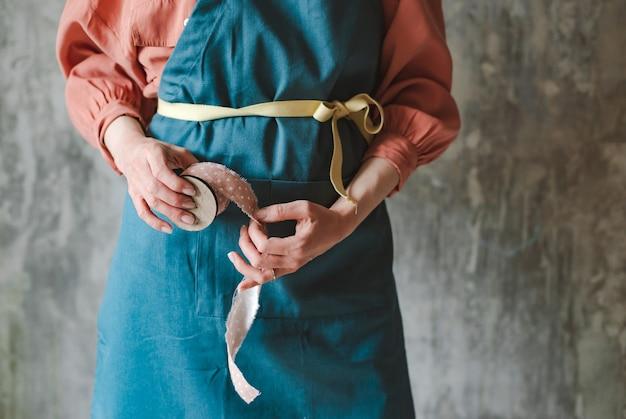 Bobine rétro en bois avec tresse à pois rose dans les mains d'une couturière dans un tablier