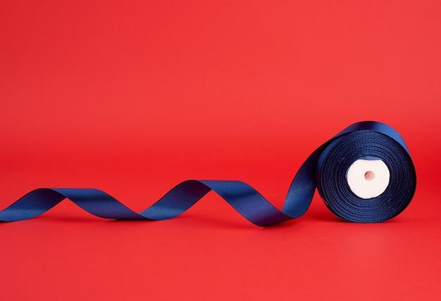 Bobine de ruban brillant en soie bleu foncé torsadé sur fond rouge