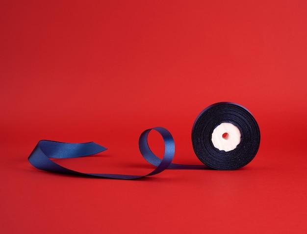 Bobine de ruban brillant en soie bleu foncé torsadé sur rouge