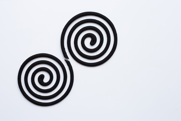 Bobines anti-moustiques en spirale noire sur fond blanc.