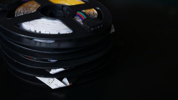 Bobines de bande led rvb sur un tableau noir. bande led pour éclairage créatif rassemblée dans une bobine noire, outils pour éclairage et effets de lumière.