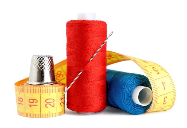 Bobines de fil, aiguille, ruban à mesurer et dé à coudre isolés