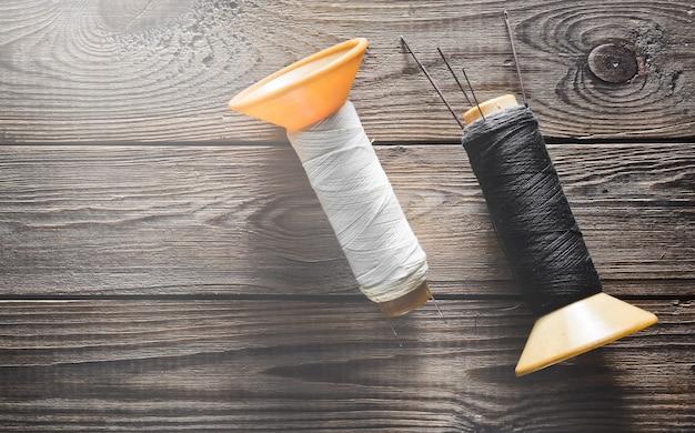 Bobines de fil blanc et noir avec des aiguilles sur bois rustique.