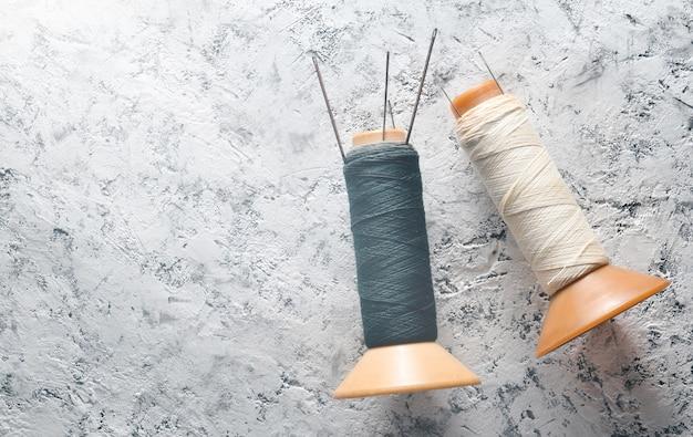 Bobines de fil blanc et noir avec des aiguilles sur du béton.