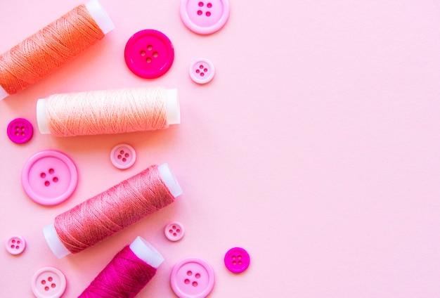 Bobines de fil et boutons dans les tons roses sur rose, pose plate
