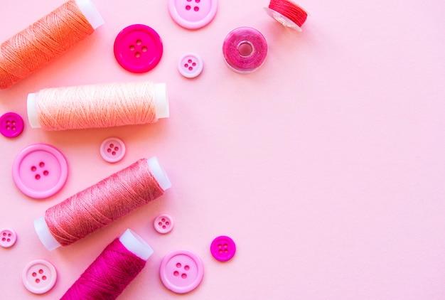 Bobines de fil et boutons dans des tons roses sur une surface rose