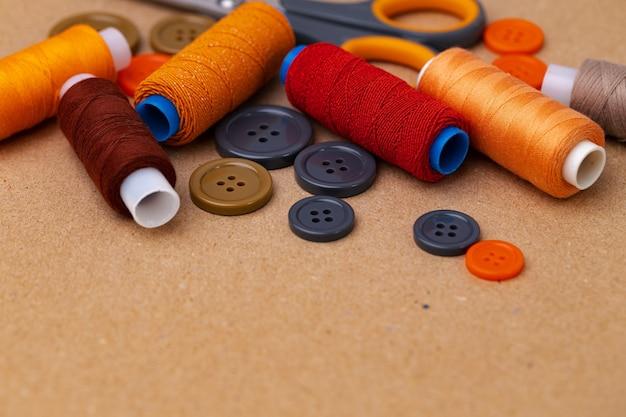 Bobines de fil et boutons sur fond beige