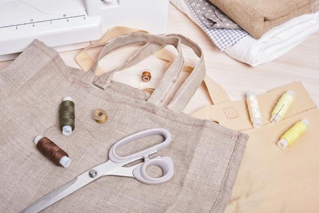 Bobines de fil, ciseaux, machine à coudre et sac en lin écologique, sac à provisions fait maison, couleurs tendance mode de vie zéro déchet