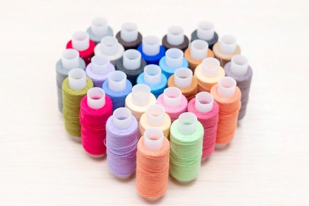 Bobines de fil à coudre de différentes couleurs. sont sur la table en forme de cœur. concept d'amour de couture.