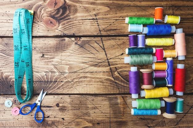 Bobines de fil de couleur disposées en rangées sur fond en bois. espace de copie.