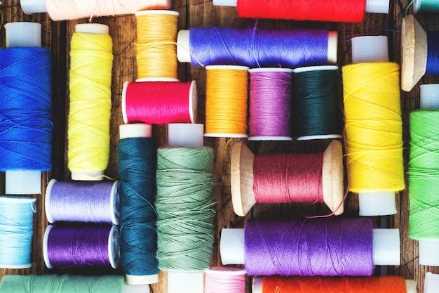 Bobines de fil de couleur disposées en rangées sur fond en bois.