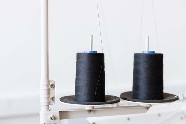 Bobines de fil dans un gros plan de machine à coudre sur fond blanc